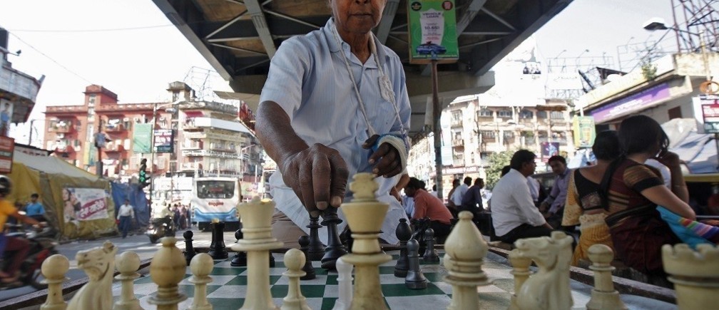 Amlandu Saha, 75, arranges chess before starting to play at an open air street chess club at Gariahat Boulevard in Kolkata November 11, 2013. According to the club's members, everyday dozens of people wait for hours for their turn to play a game of chess after finishing their day's work. With India having overtaken France as the nation with the most players rated by the World Chess Federation, the country that invented the predecessor of the strategic game is finally proving to be a hotbed of chess talent. REUTERS/Rupak De Chowdhuri (INDIA - Tags: SPORT CHESS SOCIETY) - RTX1597P