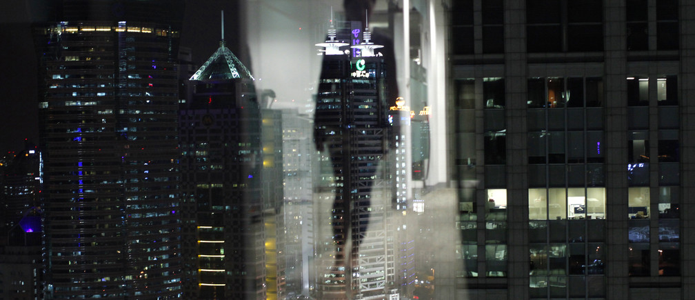 A woman is reflected in a window of an office in the financial district of Pudong in Shanghai