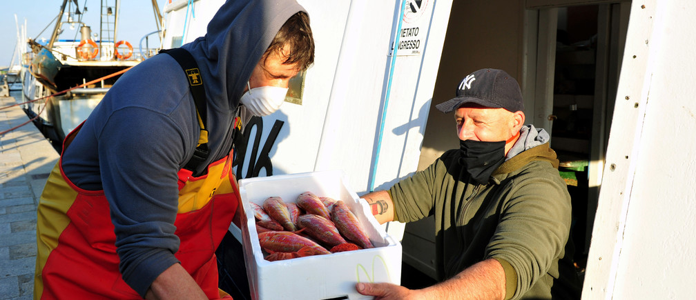 Fisherman Giuseppe Temperani gives freshly caught fish to volunteers who will deliver it to needy families, as Italy remains on lockdown to combat the spread of the coronavirus disease (COVID-19), in the Tuscan city of Castiglione della Pescaia, Italy, April 7, 2020. Giuseppe Temperani has been donating his entire catch to the poor since the crisis began. Picture taken April 7, 2020. REUTERS/Jennifer Lorenzini - RC280G92AD15