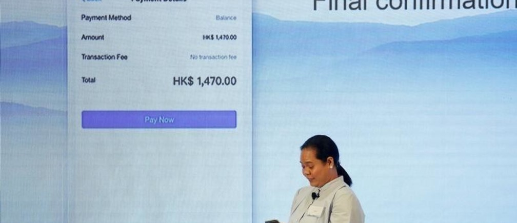 A Filipino guest demonstrates a blockchain-based remittance solution between Hong Kong and the Philippines during a news conference in Hong Kong, China, June 25, 2018.  REUTERS/Bobby Yip - RC1BCE630540