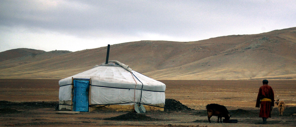 A herder walks towards a traditional Mongolian tent located on grasslands around 200km (62 miles) south-west of the Mongolian capital city Ulan Bator April 4, 2012.