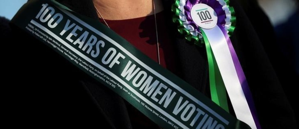 A Labour Party members of Parliament wears a rosette at an event to mark the 100th anniversary of the enfranchisment of some, but not all women, outside the Houses of Parliament in London, Britain, February 6, 2018. REUTERS/Hannah McKay