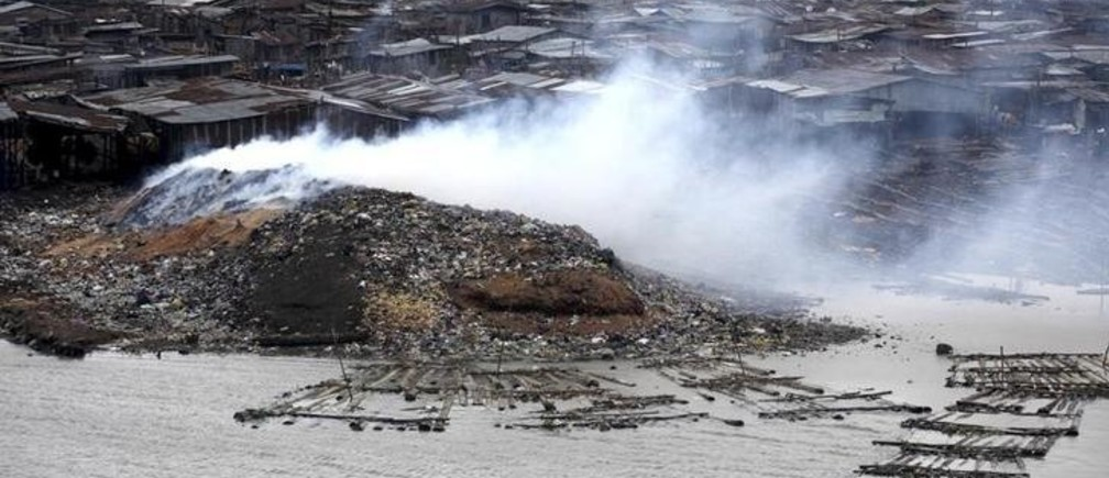Smoke rises from the waste heap at a saw-mill at a lagoon near the Makoko Riverine Slum in Nigeria's commercial capital Lagos September 15, 2009. REUTERS/Akintunde Akinleye (NIGERIA ENVIRONMENT EMPLOYMENT BUSINESS)