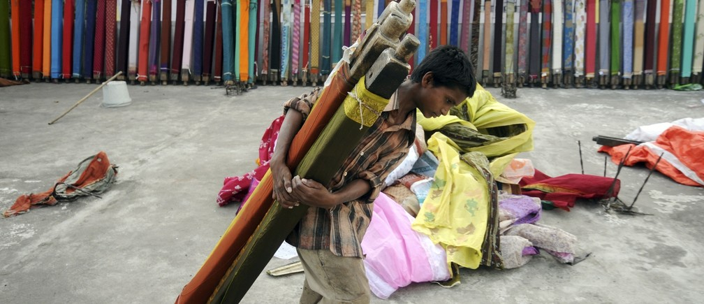 Mohammed Zakir, (13), carries rolls of sarees, a traditional cloth used for women's clothing, for drying after washing them on the terrace of a building in the southern Indian city of Hyderabad June 30, 2011.