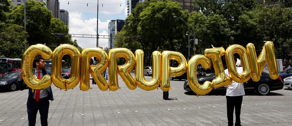 Businessmen hold balloons forming the word that reads 'Corruption' during a protest by members of the Mexican Employers' Confederation (COPARMEX) to demand senators to approve the original proposal of the National Anticorruption System, at the Angel of Independence monument in Mexico City, Mexico, June 16, 2016.
