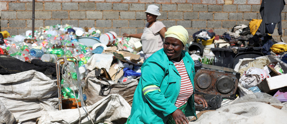 Waste pickers Abigail Kubheka and Adelina Nkopane sort out recyclable material amid the spread of the coronavirus disease (COVID-19) in Soweto, near Johannesburg, South Africa, April 20, 2020. Picture taken April 20, 2020. REUTERS/Siphiwe Sibeko - RC28AG9QMUEL