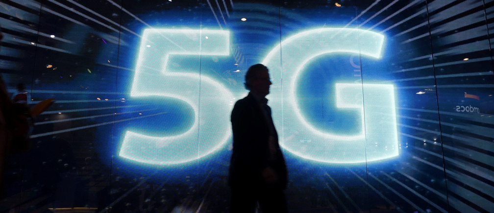 A visitors walks past a 5G sign during Mobile World Congress in Barcelona, Spain, February 28, 2017