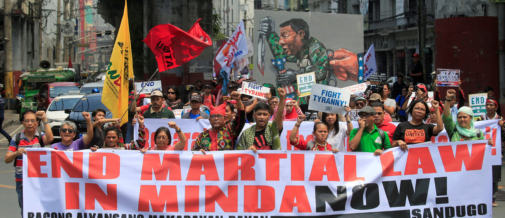 Activists display a banner and a mural of President Rodrigo Duterte to denounced the declaration of martial law in Mindanao island, one year after Islamic militants occupied parts of the southern Philippine city of Marawi during a protest outside the presidential palace in Metro Manila, Philippines May 23, 2018. REUTERS/Romeo Ranoco - RC138137AEC0