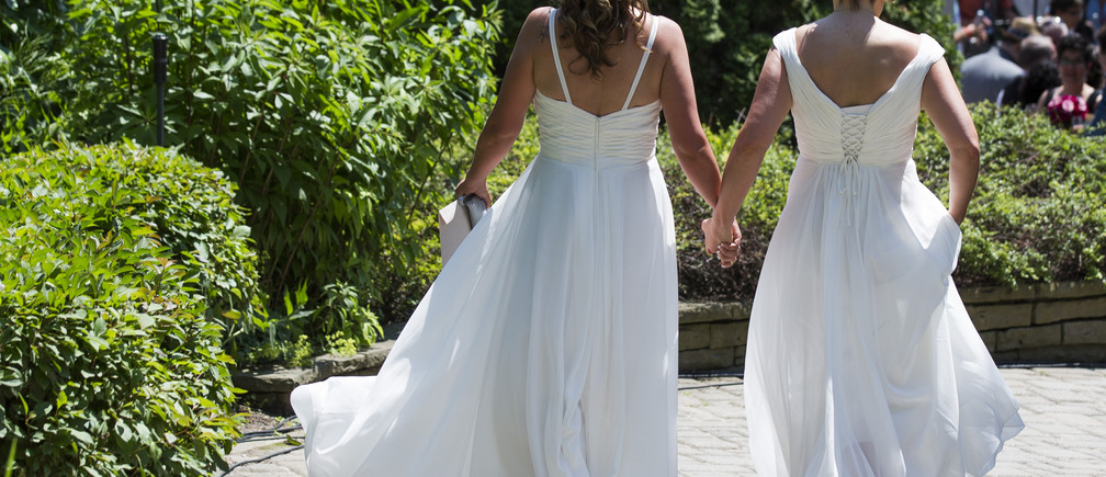 """A couple walks down a pathway to the """"The Celebration of Love"""", a grand wedding where over 100 lesbian, gay, bisexual and transgender (LGBT) couples will get married, at Casa Loma in Toronto June 26, 2014. Toronto is hosting WorldPride, a week-long event that celebrates the LGBT community. REUTERS/Mark Blinch (CANADA - Tags: SOCIETY) - RTR3VYX3"""