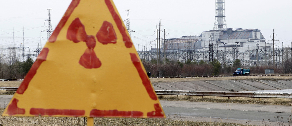 A radiation sign is seen, with a sarcophagus covering the damaged fourth reactor at the Chernobyl nuclear power plant in the background, April 4, 2011.