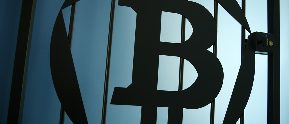 "A Bitcoin (virtual currency) logo is pictured on a door in an illustration picture taken at La Maison du Bitcoin in Paris May 27, 2015. British authorities have come out in support of digital currencies in the name of promoting financial innovation, while proposing that regulations should be drawn up to prevent their use in crime. But it is technophiles who are leading the drive to make London a real-world hub for trade in web-based ""cryptocurrencies"", of which bitcoin is the original and still most popular.   Picture taken May 27, 2015.  REUTERS/Benoit Tessier - RTX1EWRL"