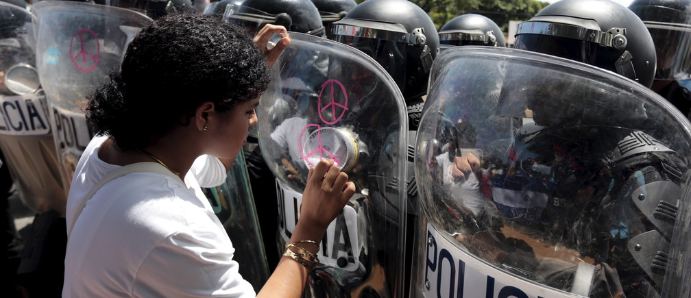 An opposition supporter draws peace signs on the shield of a riot police officer during a protest in front of the Supreme Electoral Council (CSE) building in Managua, Nicaragua August 5, 2015. The protesters said they were demonstrating to demand fairer elections in the country next year. REUTERS/Oswaldo Rivas - GF20000014620