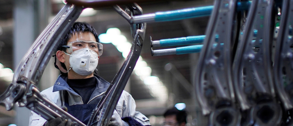 An employee wears a face mask to work on a car seat assembly line in Shanghai.