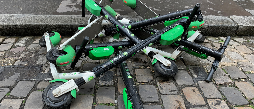 Dock-free electric scooters Lime-S by California-based bicycle sharing service Lime are stacked on Parisian cobblestones in a street of Paris, France, May 19, 2019. Picture taken May 19, 2019. REUTERS/Christian Hartmann - RC1168DDA230