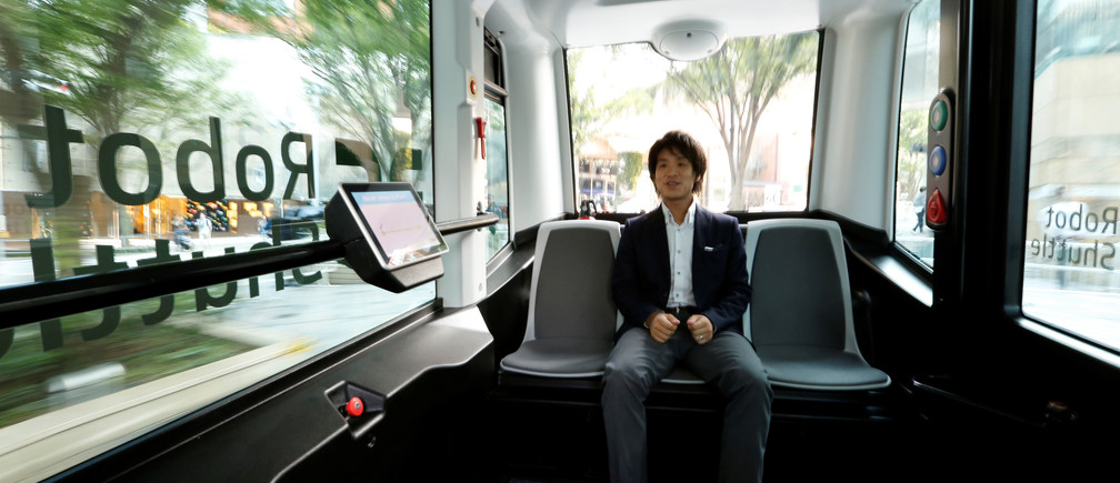 An employee of Japan's internet commerce and mobile games provider DeNA Co, rides on the company's Robot Shuttle, a driver-less, self driving bus, during its demonstration in Tokyo, Japan July 7, 2016.