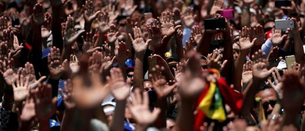 Supporters of Venezuelan opposition leader Juan Guaido, who many nations have recognized as the country's rightful interim ruler, wave their hands in El Tigre, Venezuela March 22, 2019. REUTERS/Carlos Jasso - RC1DA713C2A0
