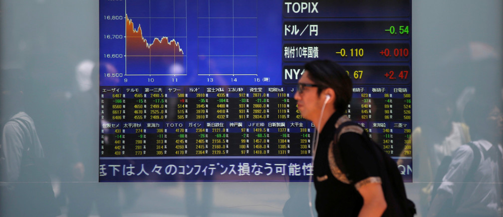 A man walks in front of a screen showing today's movements of Nikkei share average outside a brokerage in Tokyo, Japan.