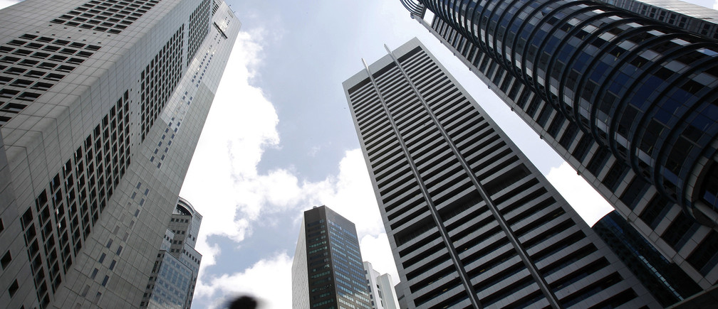 A man walks past buildings at the central business district of Singapore.