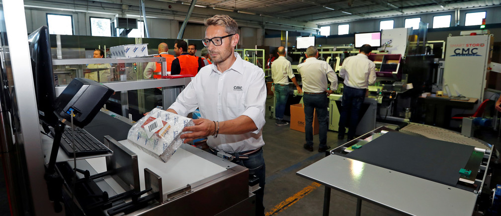 An employee scans a code on a package at a factory of Italian packaging company CMC Srl in Citta di Castello, Italy, June 25, 2019. Picture taken June 25, 2019.  REUTERS/Remo Casilli - RC1F79D03FA0