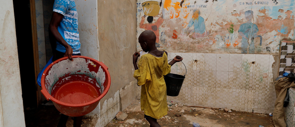 """Moussa, a Koran student, called a talibe, from Futa, carries a bucket of water to take a shower at Maison de la Gare, an organisation that helps talibe street children reintegrate into society, in Saint-Louis, Senegal, February 7, 2019. """"My parents know that I'm begging to take money back to the marabout (Koranic teacher) but they don't do anything. I don't like to beg but I'm forced. I'm being beaten up if I don't take money back,"""" Moussa said. REUTERS/Zohra Bensemra    SEARCH """"TALIBE BENSEMRA"""" FOR THIS STORY. SEARCH """"WIDER IMAGE"""" FOR ALL STORIES. - RC110AD9CD70"""