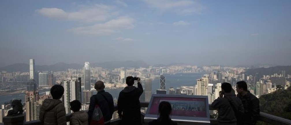 Mainland Chinese tourists view the Hong Kong skyline at the Peak in Hong Kong January 14, 2014. Launched by the Hong Kong government over a decade ago to stimulate an economy battered by the Severe Acute Respiratory Syndrome (SARS) crisis, the Hong Kong Capital Investment Entrant Scheme has proved a hit with mainland Chinese who, though technically barred, see it as a means to invest money near home without the tight controls imposed by Beijing. Although governed by Beijing, Hong Kong has a high degree of autonomy. Picture taken January 14, 2014.   REUTERS/Tyrone Siu (CHINA - Tags: POLITICS BUSINESS SOCIETY IMMIGRATION CITYSCAPE TRAVEL)