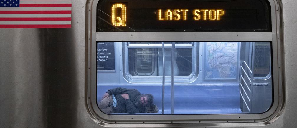 A man sleeps inside an MTA subway car, during the coronavirus disease (COVID-19) outbreak in New York City, New York, U.S., May 6, 2020. REUTERS/Jeenah Moon REFILE - CORRECTING INFORMATION - RC2UIG9ZNFSN