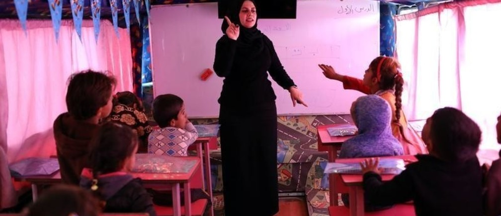 An Iraqi teacher teaches squatter children at the mobile school Bus operates by civil society in Baghdad, Iraq November 22, 2018. Picture taken November 22, 2018. REUTERS/Thaier al-Sudani - RC15843F2800
