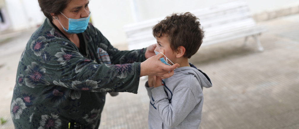 Amparo Aguilera puts a protective face mask on her grandchild Kilian, 6, after restrictions were partially lifted for children, during the coronavirus disease (COVID-19) outbreak, in Igualada, Spain April 26, 2020. REUTERS/Nacho Doce - RC2GCG90NK6P