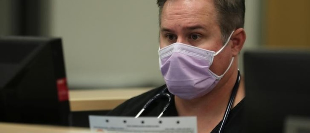 Emergency room nurse Richard Horner wears a mask as he deals with flu patients at Palomar Medical Center in Escondido, California, U.S., January 18, 2018.      REUTERS/Mike Blake