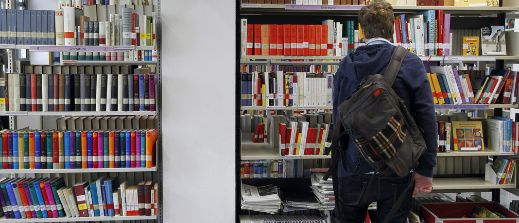 A man looks at books in Goethe Institute's library in Barcelona February 1, 2013. Barcelona's Goethe Institute offers more than 170 German courses every year. In the last two years they have seen the number of students grow by 75 percent, most of them people under 25 who want to seek a better future in Germany, according to the centre director, Marion Haase. Picture taken February 1, 2013. REUTERS/Albert Gea (SPAIN - Tags: BUSINESS EMPLOYMENT EDUCATION) - RTR3DCZ2