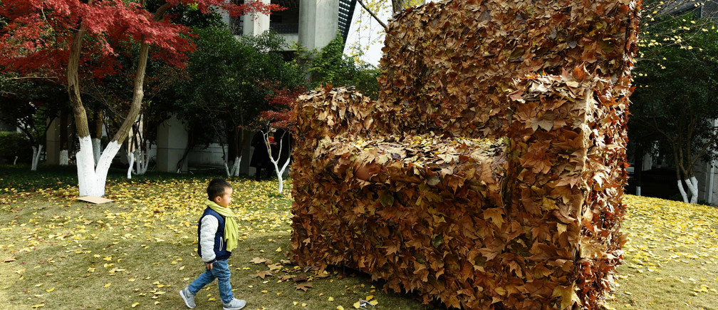A child walks to an installation made from fallen leaves by college students, in shape of a sofa, to call for people's attention to environment protection, in Hangzhou, Zhejiang province, China, December 6, 2016.