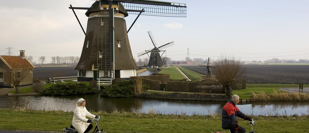 "Two Dutch bicyclists pass one of four windmills of the Viermolengang, built in 1785, in Zevenhuizen, the Netherlands, February 7, 2007. To raise money and draw tourists, the Dutch Windmill Association has proclaimed 2007 ""The Year of the Windmill"" in the hopes of attracting tourists and investment. Photo taken February 7, 2007.   REUTERS/Michael Kooren (NETHERLANDS) - GM1DUPIWQEAA"