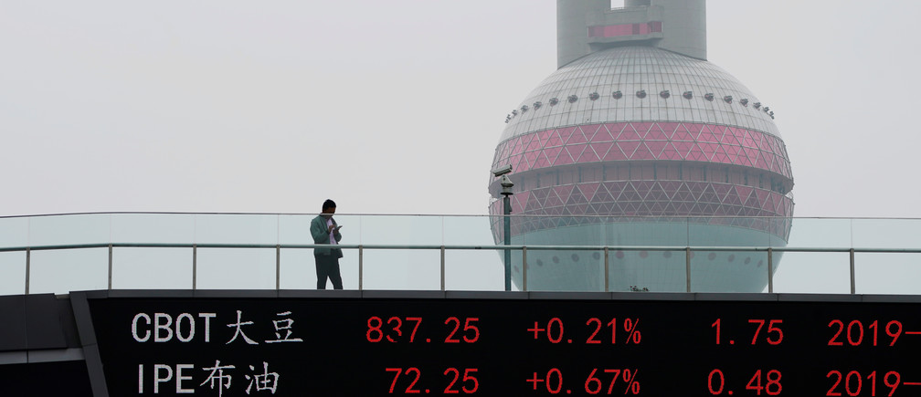 A man uses his phone above an electronic board showing the CBOT soybean futures (above) on a pedestrian overpass at Lujiazui financial district in Shanghai, China May 16, 2019.  REUTERS/Aly Song