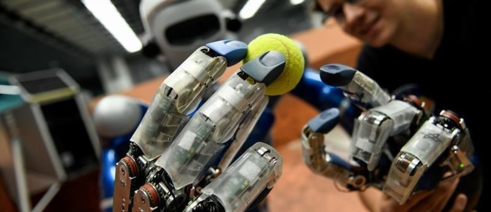 Humanoid robot Justin holds a tennis ball in a laboratory at the German Aerospace Center (DLR) in Wessling, near Munich, Germany, October 4, 2018. Picture taken October 4, 2018.