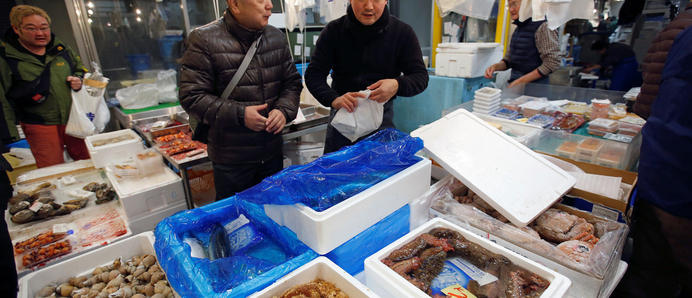 Masatoshi Fukutsuna, chef and owner of sushi restaurant Eiraku, chats with a wholesaler at Toyosu Fish Market in Tokyo, Japan December 11, 2018. Picture taken December 11, 2018. To match Insight JAPAN-SUSHI/LAST-RESTAURANT. REUTERS/Issei Kato - RC1696A278F0
