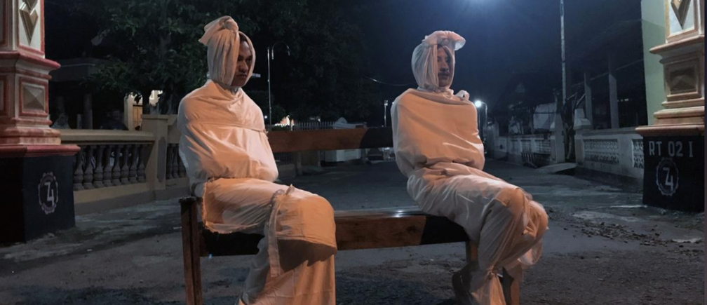 Volunteers Deri Setyawan, 25, and Septian Febriyanto, 26, sit on a bench as they play the role of 'pocong', or known as 'shroud ghost', to make people stay at home amid the spread of coronavirus disease (COVID-19), outside the gate of Kepuh village in Sukoharjo regency, Central Java province, Indonesia, April 1, 2020.