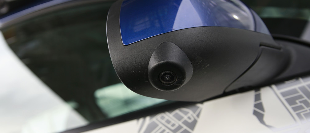 A navigational camera on the wing-mirror of a modified Nissan Leaf, a driverless car