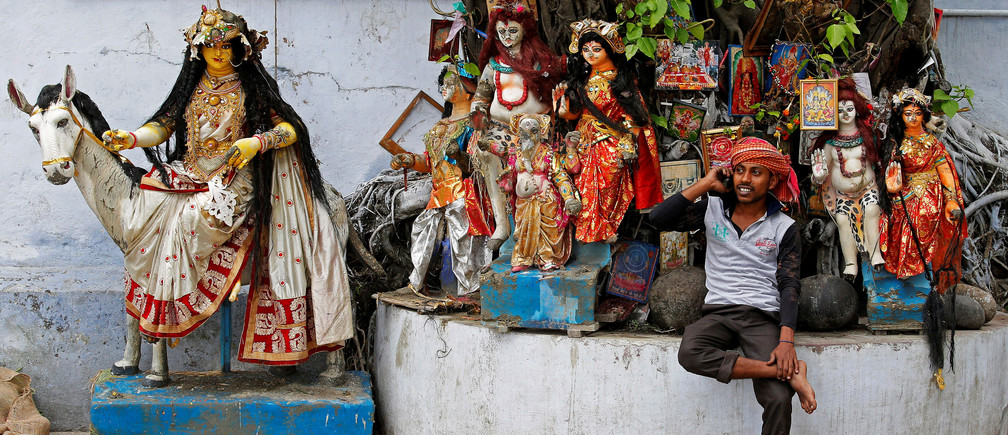 A labourer speaks on his mobile phone as he takes rest in front of idols of Hindu deities which are kept under a tree at a market area in Kolkata, India, April 2, 2018. REUTERS/Rupak De Chowdhuri     TPX IMAGES OF THE DAY - RC1570C0DAF0