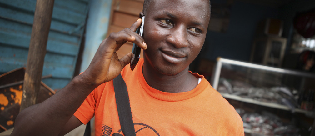 A man makes a call on a mobile phone in Sierra Leone's capital Freetown December 13, 2012. While mobile phone usage has exploded across Africa over the last decade, transforming daily life and commerce for millions, it's a revolution that has left behind perhaps two thirds of its people. Poor or no reception outside the towns helps explain why the continent's mobile penetration, in terms of the percentage of the population using the service, is far lower than previously thought, and the cost of providing that service to impoverished, sparsely populated areas remains prohibitive.  Picture taken December 13, 2012. REUTERS/Simon Akam  (SIERRA LEONE - Tags: BUSINESS TELECOMS SOCIETY) - GM1E91V1KRN01