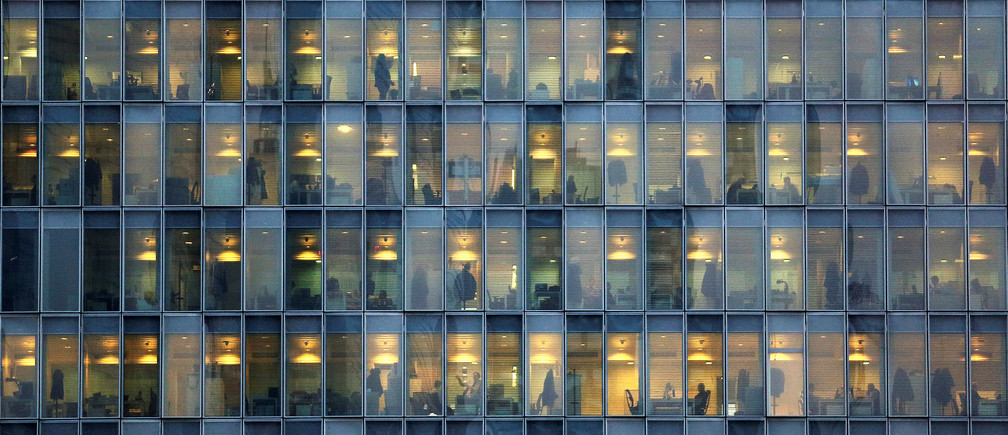 Lights are on as people work in their offices in a skyscraper in downtown Milan, February 17, 2015.