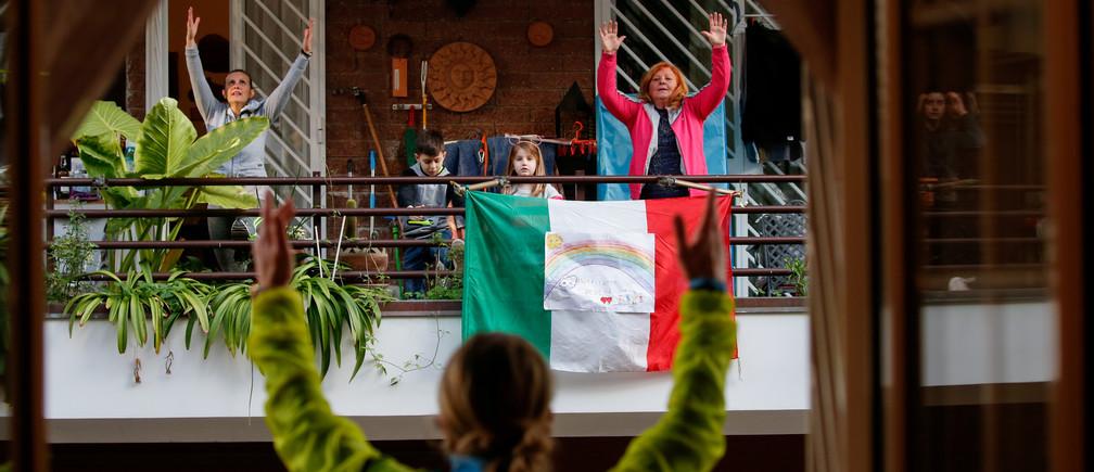 L'entraîneur personnel Antonietta Orsini fait un cours d'exercice pour ses voisins depuis son balcon alors que les Italiens ne peuvent pas quitter leur domicile en raison de l'épidémie de coronavirus (COVID-19), à Rome, en Italie, le 18 mars 2020.