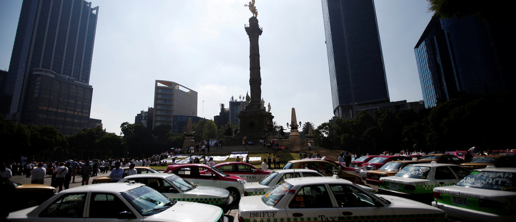 Taxis are parked during a protest against the lack of regulation of ride-hailing services like Uber and Cabify, at the Angel of independence monument in Mexico City, Mexico October 12, 2016. REUTERS/Carlos Jasso    - RTSRZZT