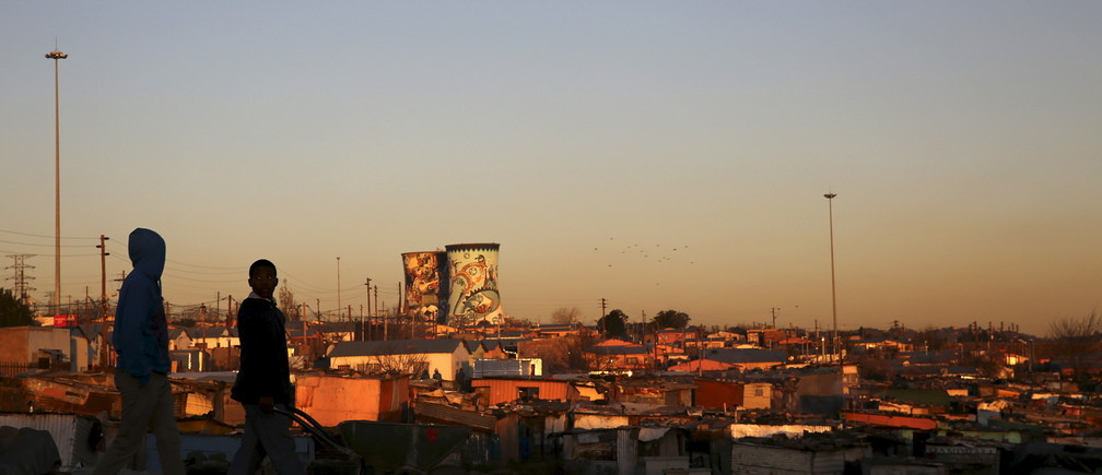 Unused cooling towers are seen overlooking an informal settlement as locals walk before sunset in Soweto, South Africa August 5, 2015. REUTERS/Siphiwe Sibeko - RTX1N78T