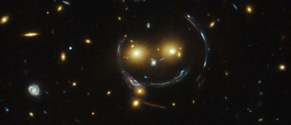 """The galaxy cluster SDSS J1038+4849 is pictured in this undated handout image taken with the NASA/ESA Hubble Space Telescope. As a result of the phenomenon of gravitational lensing, it seems to be smiling. In the case of this """"happy face""""?, the two eyes are very bright galaxies and the smile lines are actually arcs caused by strong gravitational lensing.  Galaxy clusters are the most massive structures in the Universe and exert such a powerful gravitational pull that they warp the spacetime around them and act as cosmic lenses which can magnify, distort and bend the light behind them. This phenomenon, crucial to many of Hubble's discoveries, can be explained by Einstein's theory of general relativity."""