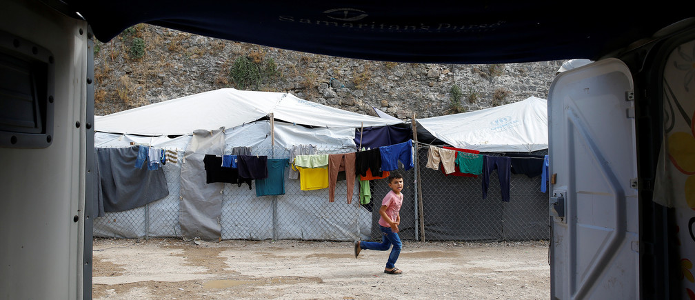 A boy runs inside the Souda municipality-run camp for refugees and migrants, on the island of Chios, Greece.
