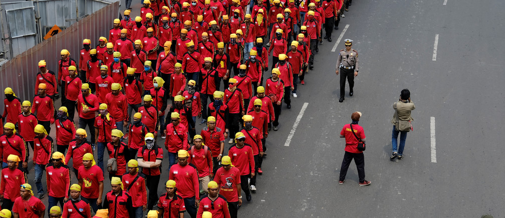 A police officer walks beside a group of Indonesian workers marching to mark May Day in Jakarta, Indonesia, May 1, 2017. REUTERS/Beawiharta - RC13ABE93310