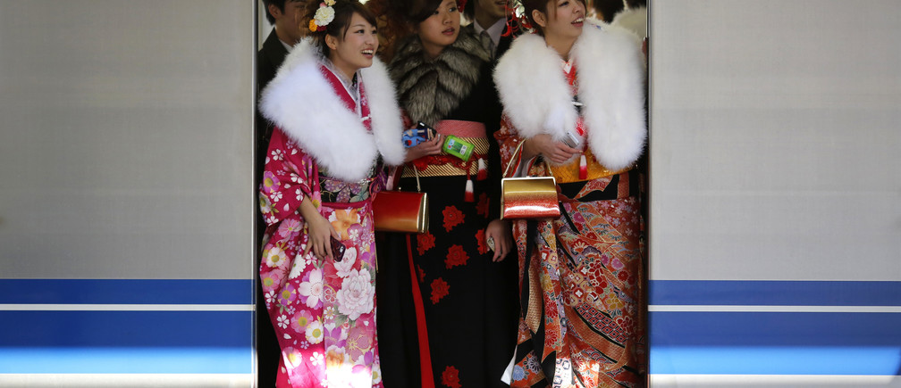 Japanese women in kimonos ride a train after a ceremony celebrating Coming of Age Day at an amusement park in Tokyo January 13, 2014. According to a government announcement, about 1,210,000 men and women who were born in 1993 reached coming of age this year and the number is 10,000 less people than last year. The figure is the smallest number since the government started counting in 1968. REUTERS/Yuya Shino (JAPAN - Tags: SOCIETY TPX IMAGES OF THE DAY) - RTX17C63