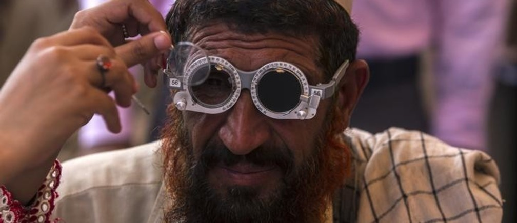 An Afghan refugee has his eyes tested at a health clinic set up by the United Nations High Commissioner for Refugees (UNHCR) to mark World Refugee Day in Islamabad June 20, 2014. World Refugee Day, an occasion that draws attention to those who have been displaced around the globe, falls on June 20.