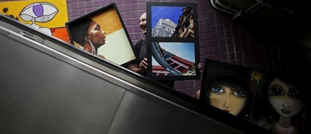"""Artists carry their creations on an escalator in Consolacao subway near Paulista avenue during a mobile exhibition named """"Walking Gallery"""", in Sao Paulo May 23, 2015. REUTERS/Nacho Doce"""