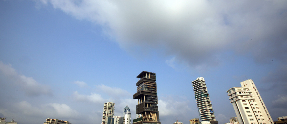 A view of the new house (C) of Mukesh Ambani, chairman of Indian energy company Reliance Industries, in Mumbai October 23, 2010. Ambani, his wife and three children have moved into the 27-story building, named Antilia, after a mythical island, local media reported. The building which contains a health club, swimming pool, three helipads and a 50 seater cinema is estimated to be worth over $1 billion, according to media reports. Picture taken October 23, 2010. REUTERS/Danish Siddiqui (INDIA - Tags: SOCIETY BUSINESS) - GM1E6AO1LSO01